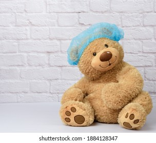 brown teddy bear sits in protective medical disposable blue cap against a background of a white brick wall. Protective accessories from the virus during an epidemic