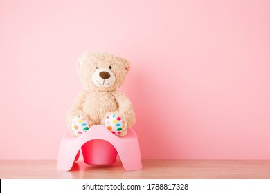 Brown teddy bear sitting on baby potty on floor. Front view. Closeup. Empty place for text on light pink background. Pastel color.