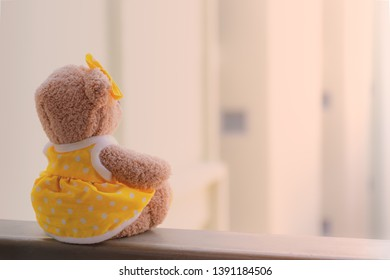 Brown teddy bear sitting vacant alone at the terrace with blurred background, Absent-minded and waiting for someone concept.