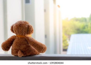 Brown teddy bear sitting vacant alone at the terrace with nature blurred background, Absent-minded and waiting for someone concept.