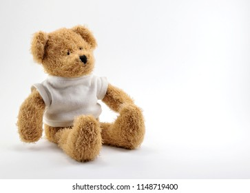 Brown Teddy bear toy in a white knitted sweatshirt, on a white background.