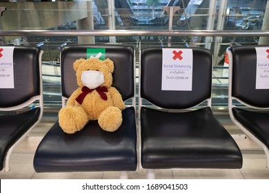 The brown teddy bear wearing a medical face mask to protect and prevent the coronavirus (COVID-19) infection sitting on the public chair alone and away from others, social distancing concept
