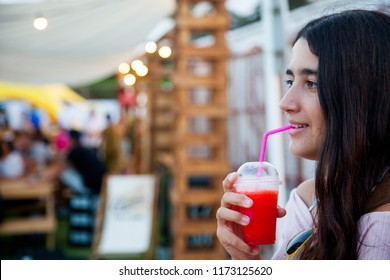 Brown teenage girl drinks an icy red drink
