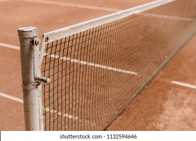 brown tennis court with tennis net and marking lines