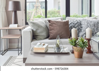 Brown and texture pillows on beige sofa with candles on wooden top table