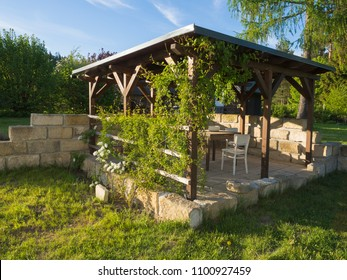 brown tiber wooden gazebo or pergola with climbing plants and flowers, table and chairs and surrounding sandstone wall, green grass blue sky in afternoon golden light