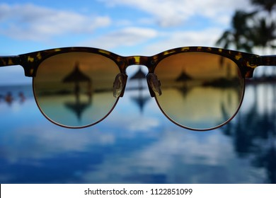Brown tortoiseshell sunglasses in focus with blurred background of hotel pool and palm trees