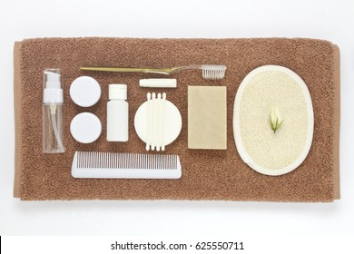Brown towel and bathroom amenities kit isolated on white background.
