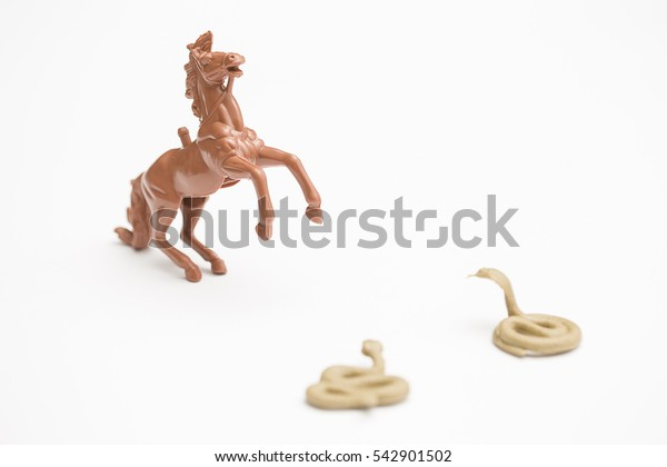 Brown toy horse threatened by two snakes