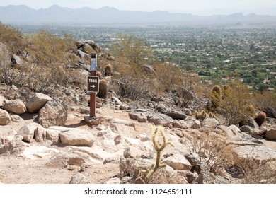 Brown trail sign on the rocky path to the top of Camelback mountain in Scottsdale, Arizona