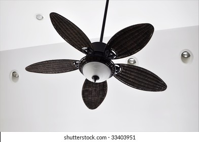 brown tropical ceiling fan against white walls with recessed lighting fixtures