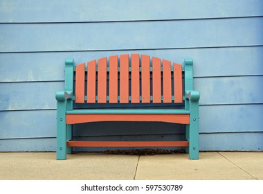 Brown and turquoise bench in front of a pale blue wooden house facade