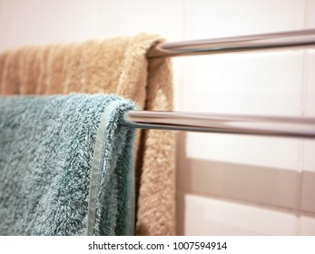 Brown and turquoise towels hanging on towel racks made of chrome against white tiled bathroom wall