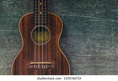 Brown ukulele guitar portrait on texture Wall plaster ,Vintage dark tone holiday relax break time with music or art concept with copy space for your text