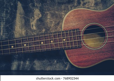 Brown ukulele guitar portrait on texture Wall plaster ,Vintage dark tone holiday relax break time with music or art concept