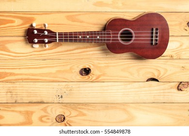 brown ukulele rests on a wooden floor. Use as Wallpaper