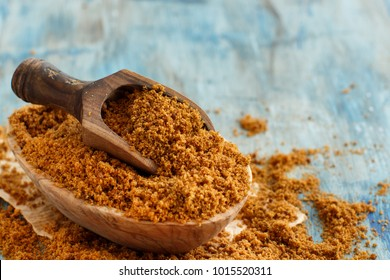 Brown unrefined cane sugar with a spoon close up