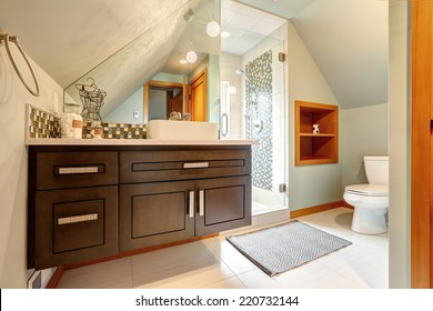 Brown vanity cabinet with mirror, glass door shower in small bathroom with vaulted ceiling