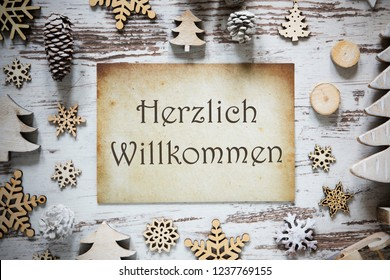 Brown Vintag Paper With German Text Herzlich Willkommen Means Welcome. Rustic Christmas Decoration Like Tree, Fir Cone And Snowflakes. White Wooden Background