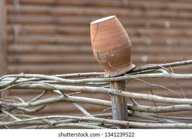 Brown vintage ceramic pot on wooden fence. Izborks, Russia travel.