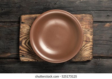 Brown vintage empty plate on a old cutting board on dark wooden background, top view