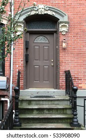 Brown vintage entry door decorated with arch and corbels. New York. USA.