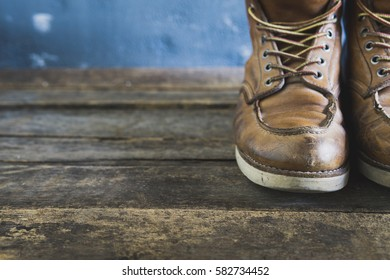 brown vintage leather boots on wooden background