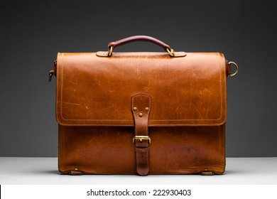 Brown Vintage leather briefcase with strap and brass buckle,