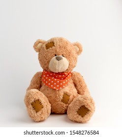 brown vintage teddy bear with patches, white background,  white polka dot scarf is tied around his neck