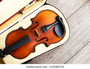 Brown violin in case over wooden background. Art and music background. Favorite string instrument. Top view.