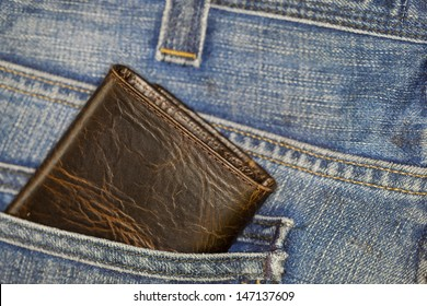 Brown wallet in blue jeans back pocket