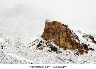 Brown and warm colored Cliff face rising from the snow-covered valley with a foggy and cold backdrop