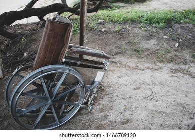 A brown weathered wheel chair abandoned at the beach near a homeless encampment in Hawaii. Later on a man unscrewed one wheel and walked away with it.