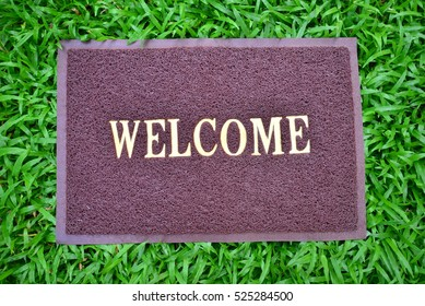brown welcome carpet on green grass