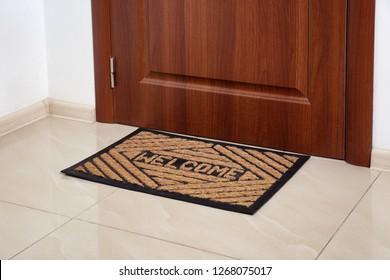 Brown welcome doormat at door in hall