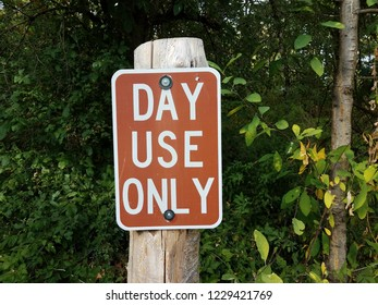 brown and white day use only sign on wood post in the forest