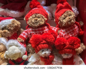 Brown and white plush teddy bears in red Christmas caps with pompons and red sweaters and scarfs.