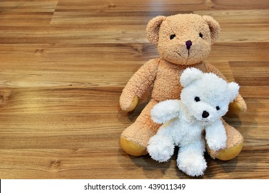 brown and white teddy bear doll are sit on wood floor,love concept