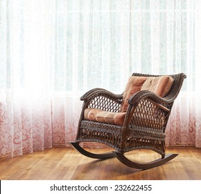 Brown wicker rocking chair against the window's curtains, indoor composition
