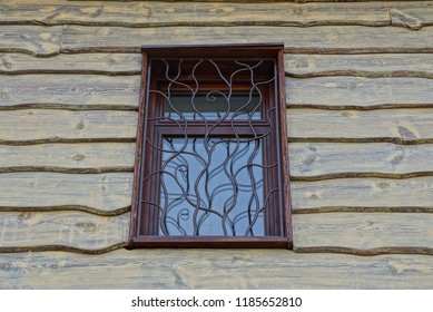brown window with a lattice on the wall of wooden boards