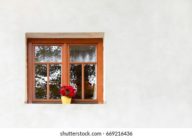 Brown window with a red flower in a pot on a white wall