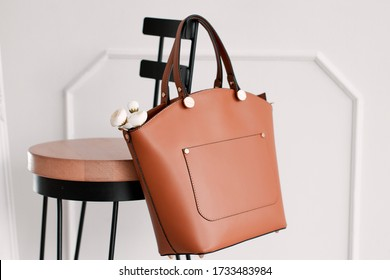 A brown women's bag on a hanging chair.