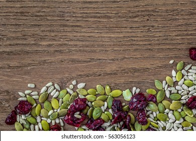 Brown Wood Background with Pumpkin Seeds, Sunflower Seeds, and Dried Cranberries, with Open Space for Text or Copy.