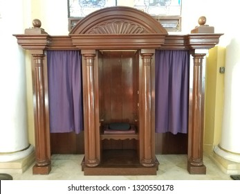 brown wood confession booth with purple curtain