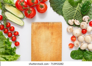 Brown wood cutting board, border of fresh organic vegetables, fruits and nuts on white background. Healthy natural food on table with copy space, top view