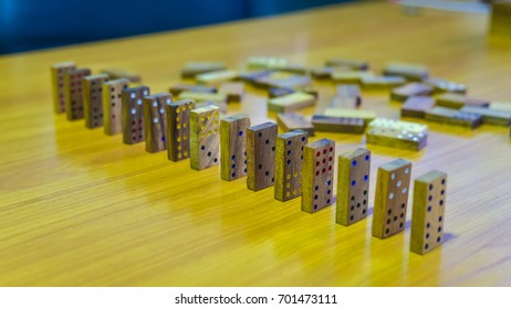 Brown wood dominoes line stand in a row on a wooden table
