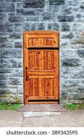 Brown wood door with black metal hinges in stone building.