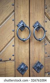 Brown wood doors with iron door knobs close up