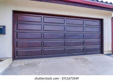 Brown wood panel door of attached garage in San Diego California neighborhood