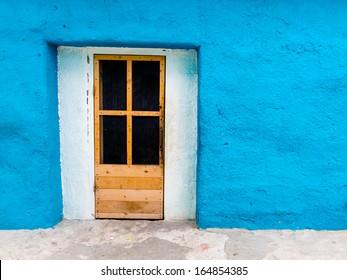 Brown Wood Screen Door on Blue Stucco Home